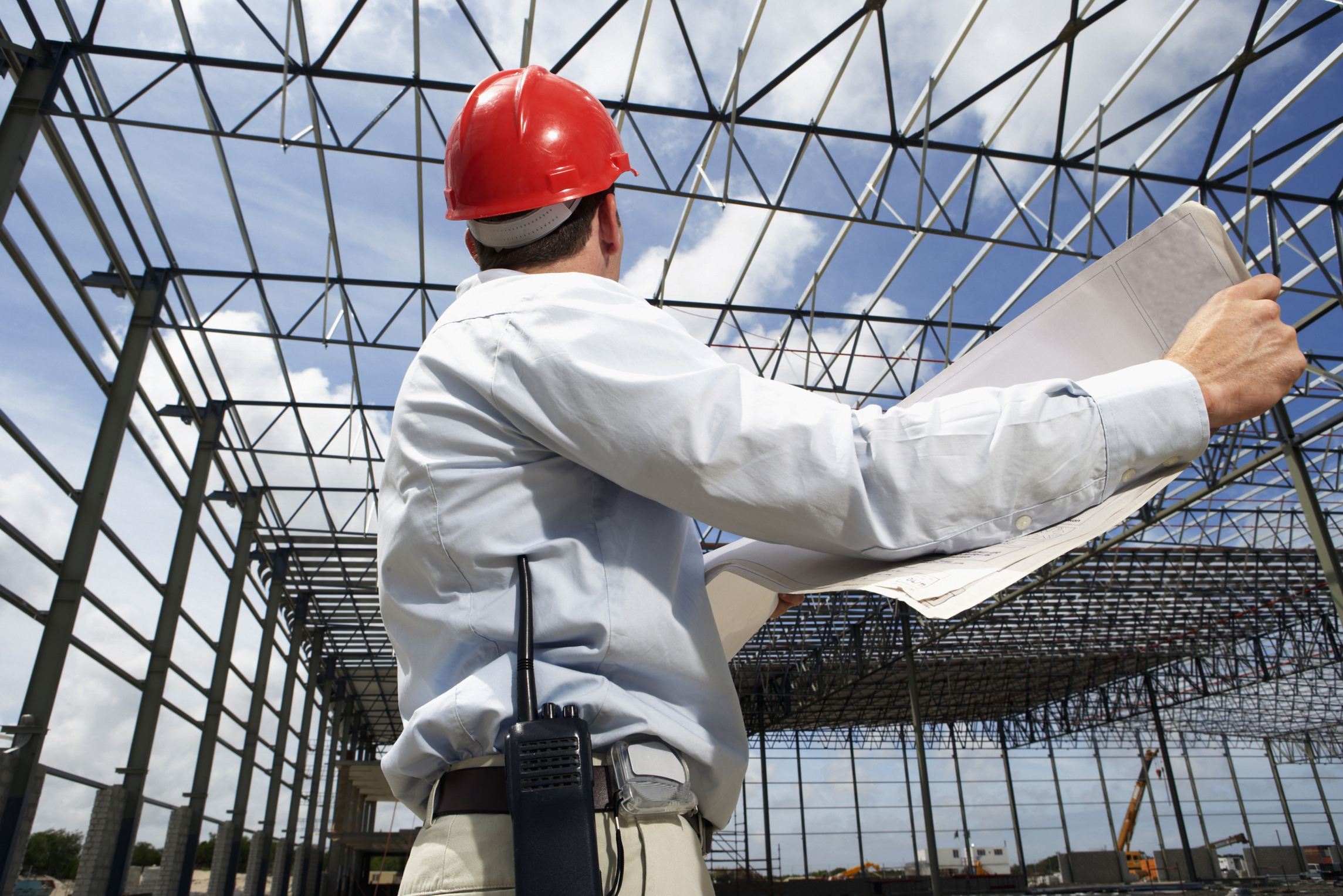 Construction Worker Holding Plans on Building Site